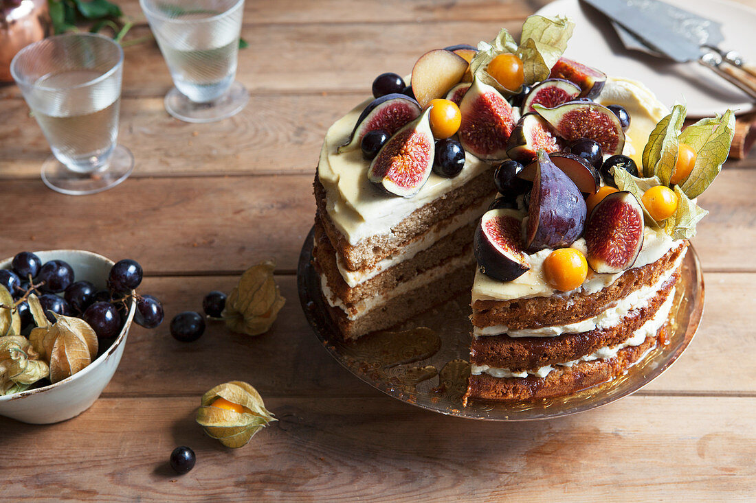 Sliced honey layer cake decorated with fresh fruits