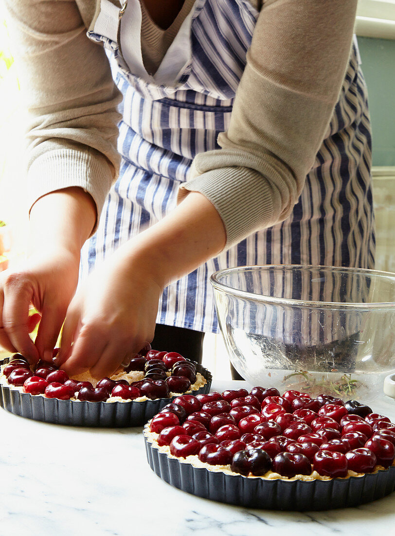Hand arranging cherries into frangipane tart