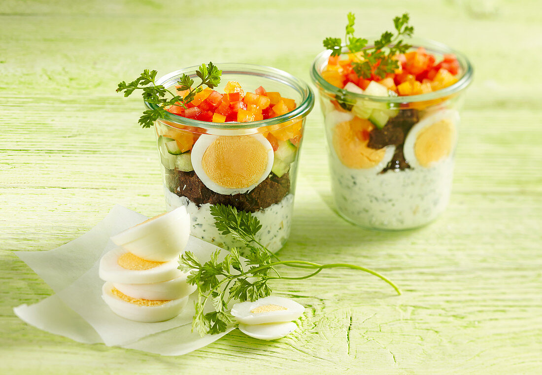 Boiled eggs with pumpernickel and herb quark in glass jars