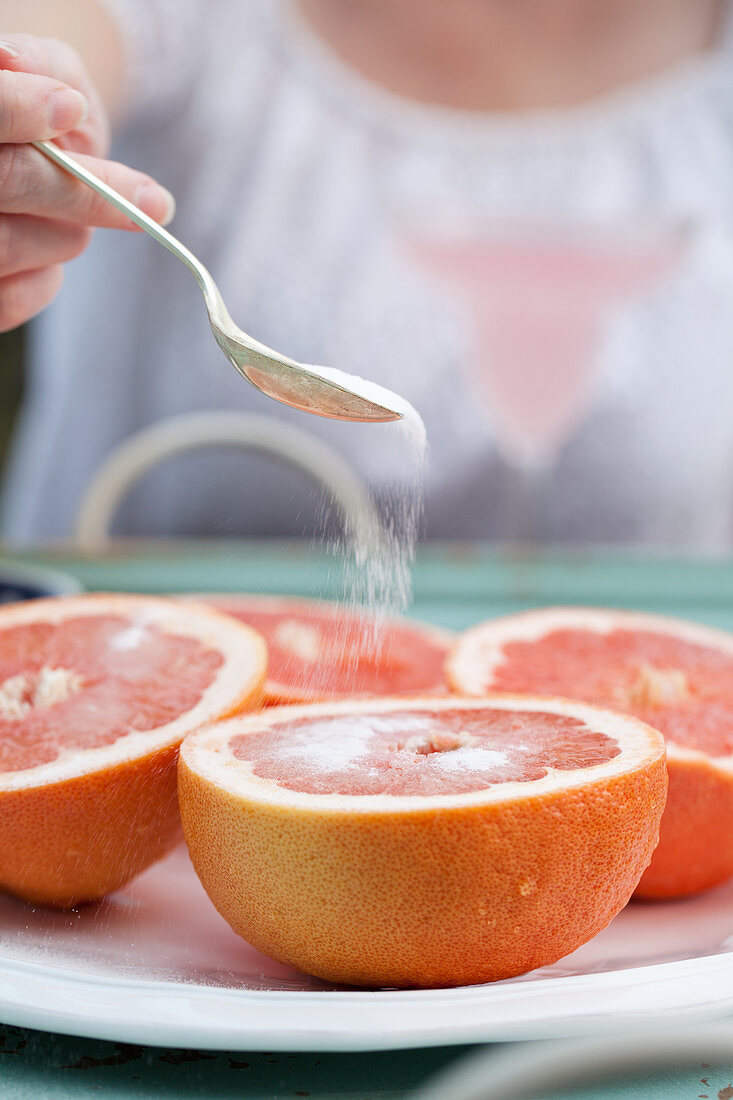 A woman sprinkling sugar onto a platter of grapefruit halves