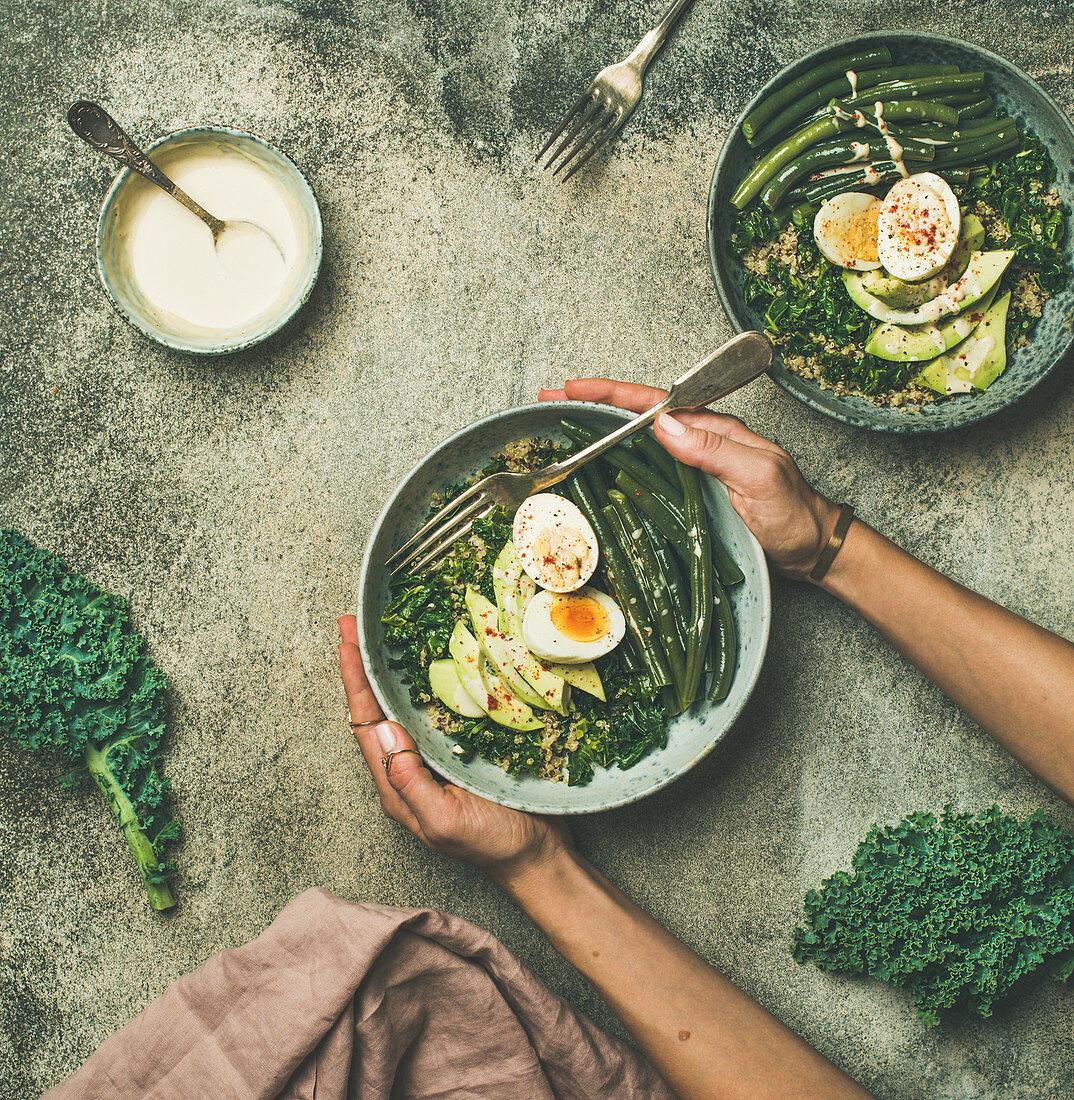 Quinoa, kale, beans, avocado, egg with creamy tahini dressing bowls over grey concrete background