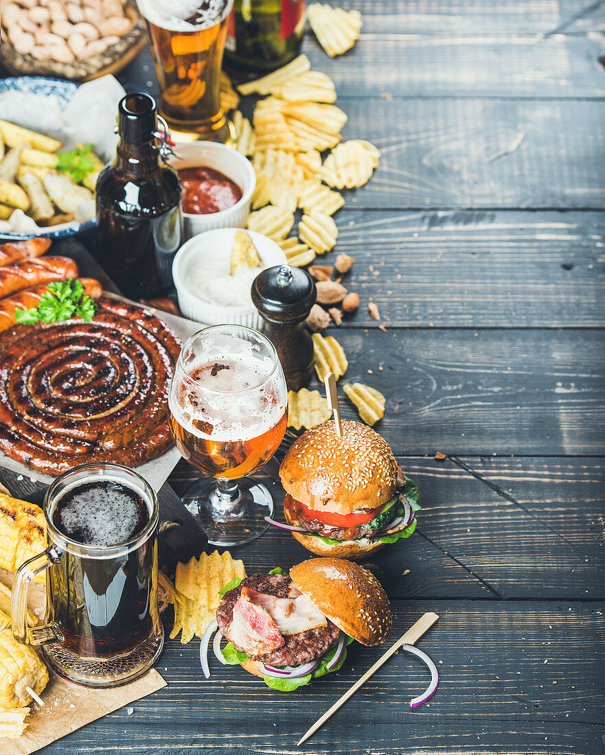 Variety of beers, grilled sausages, burgers, fried potato, corn, chips and sauces on dark wooden background