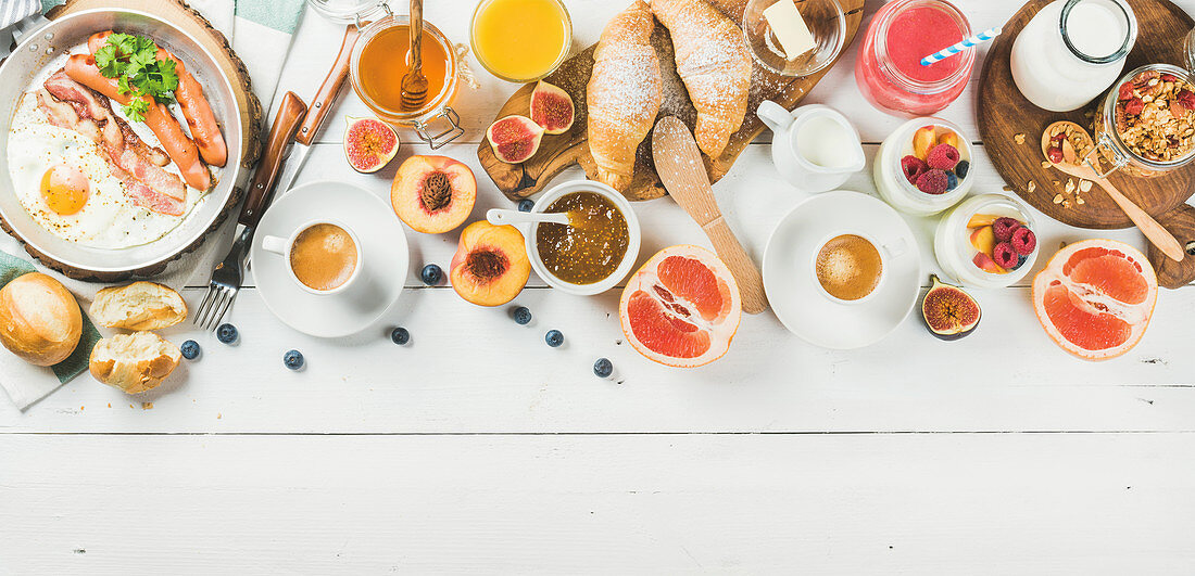 Fried egg with sausages and bacon, bread, croissants, jam, fruit, smoothie, juice, yogurt, granola with milk and coffee on white wooden background