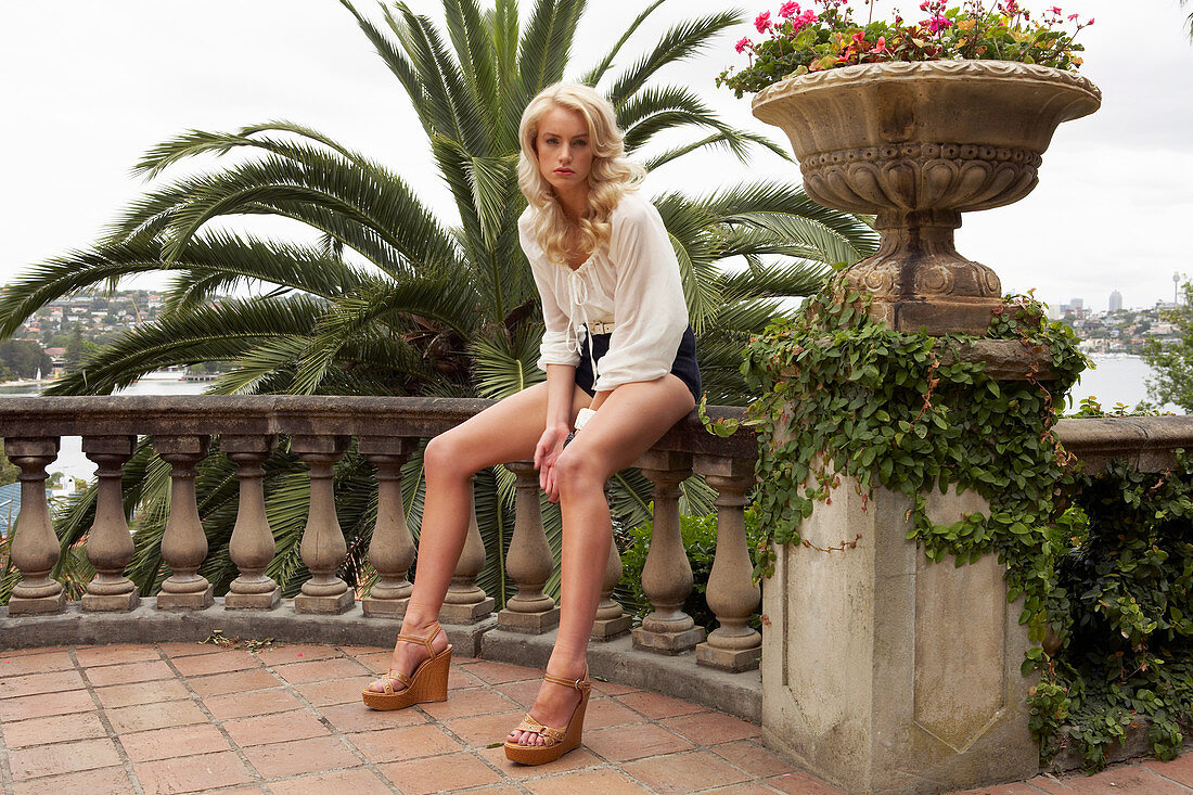 Blonde, langhaarige Frau in cremefarbener Bluse und Shorts auf der Terrasse