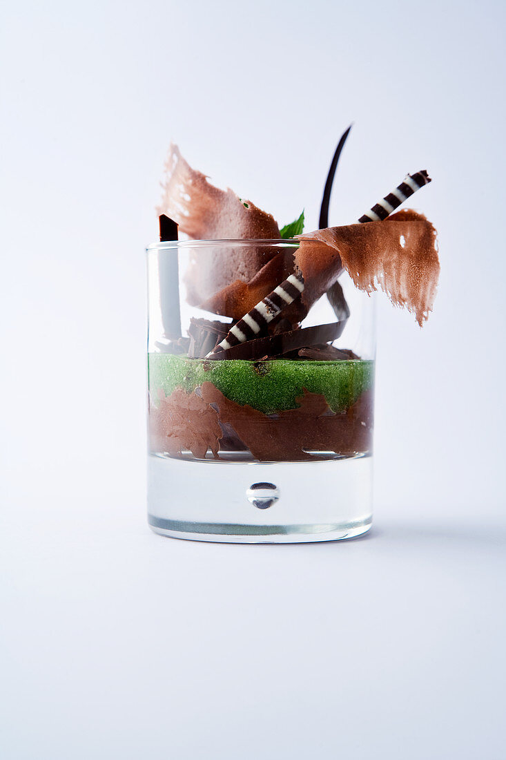Chocolate cream with mint soup in a dessert glass against a white background
