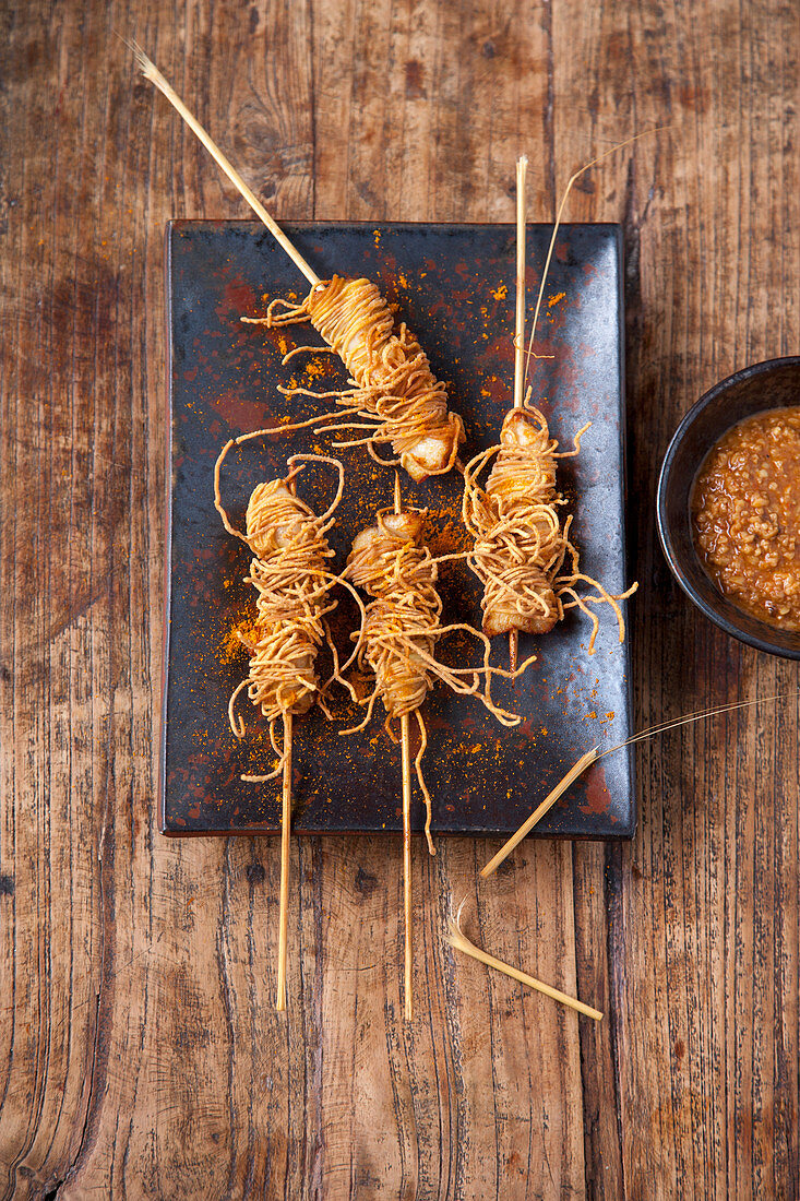 Chicken satay in a crispy pasta coating with peanut sauce