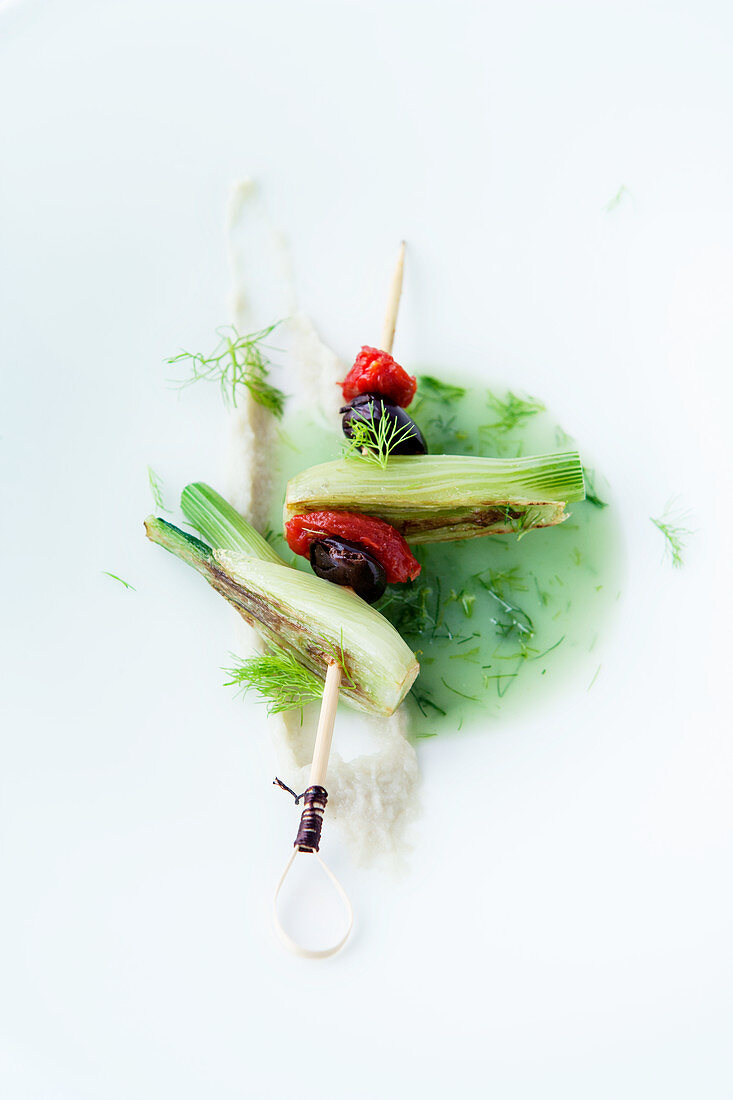 Fennel broth with a skewer of fennel, tomato and olive