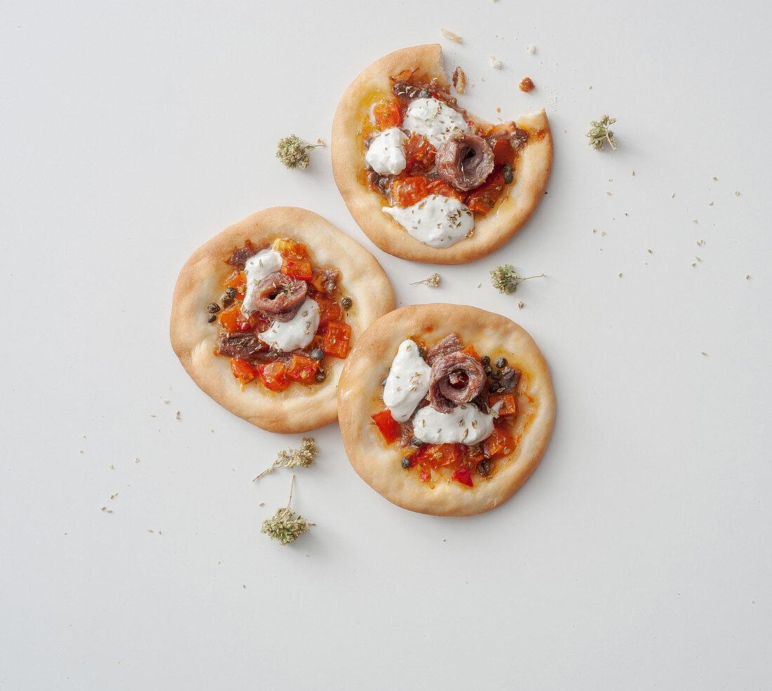 Mini pizzas with tomatoes, capers, anchovies, oregano and burrata