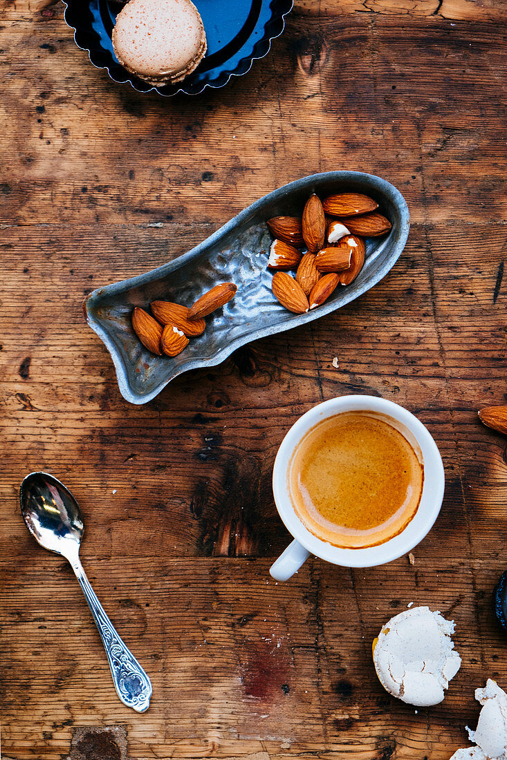 A cup of coffee with a brown macaron and almond nuts on a wooden table
