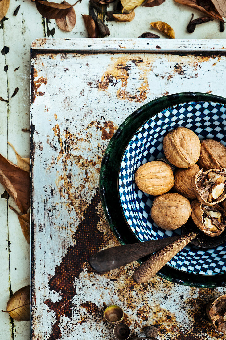 Walnuts in a blue bowl with autumn leaves