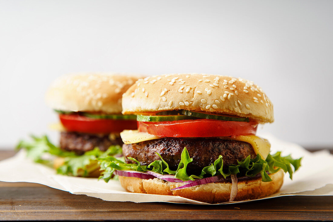 Classical burger with grilled meat, tomatoes, cheese, onion, cucumber and lettuce