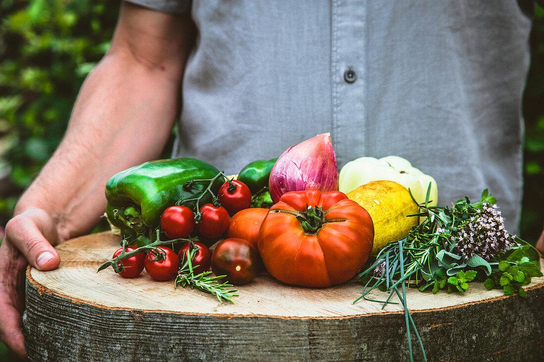 Hände halten Holzscheibe mit frisch geerntetem Gemüse