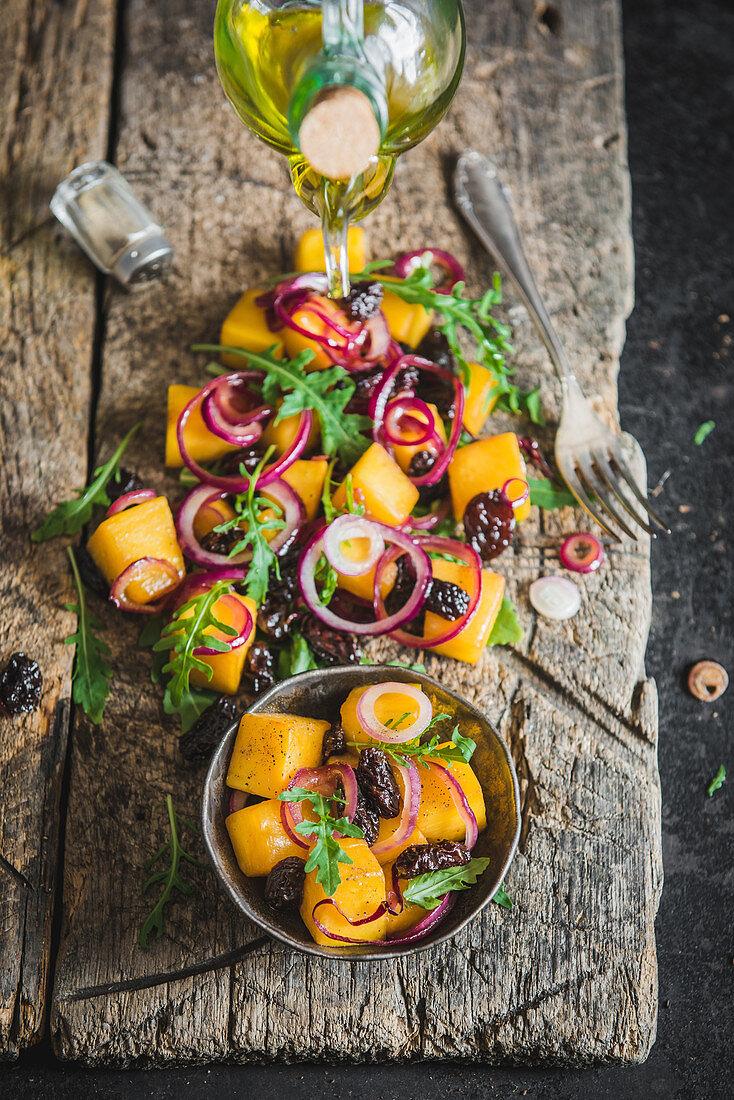 Pumpkin salad with red onion, rocket and raisins