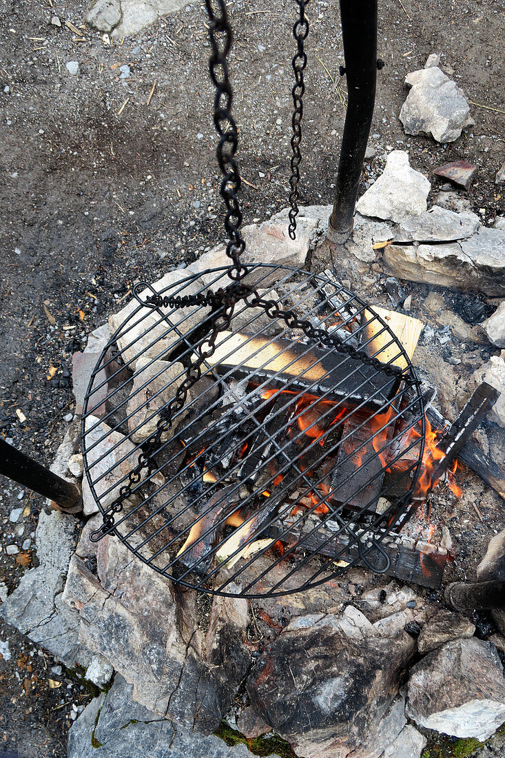A hanging barbecue grate over a fire