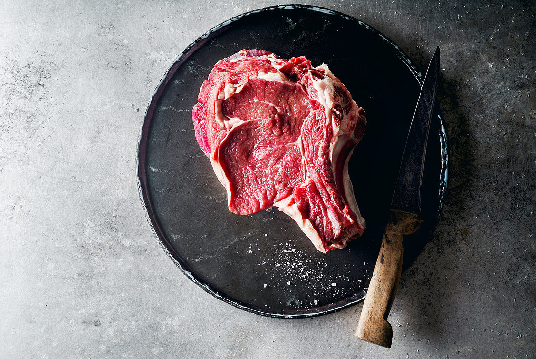 Raw beef steak with a knife on metallic background