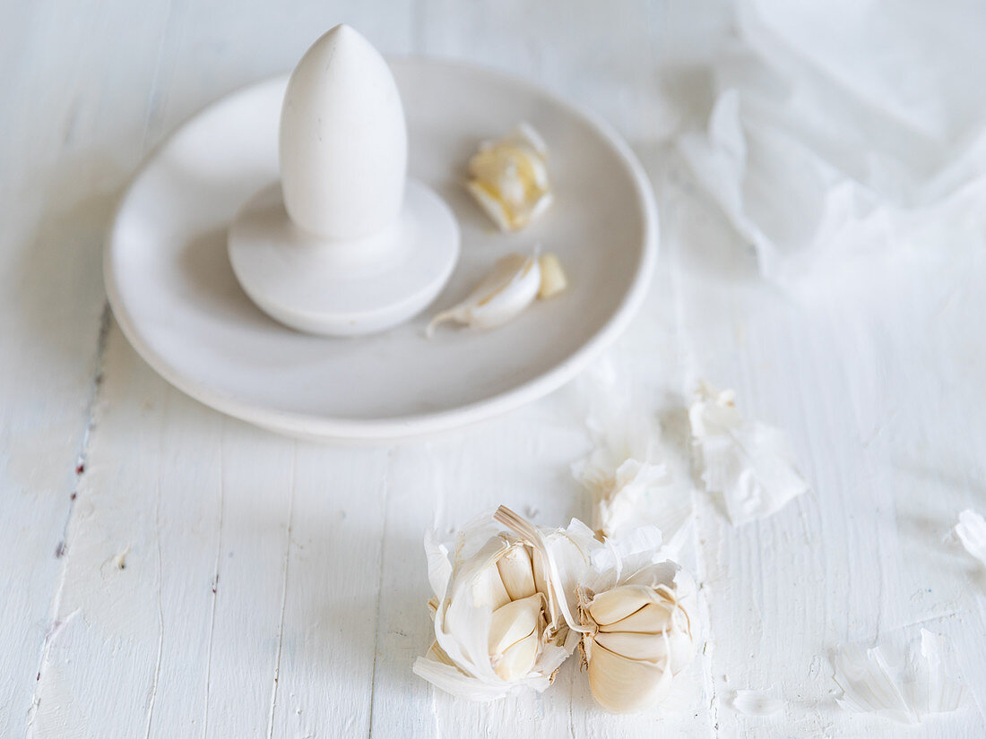 Garlic cloved in a porcelain flat mortar with spear pestle