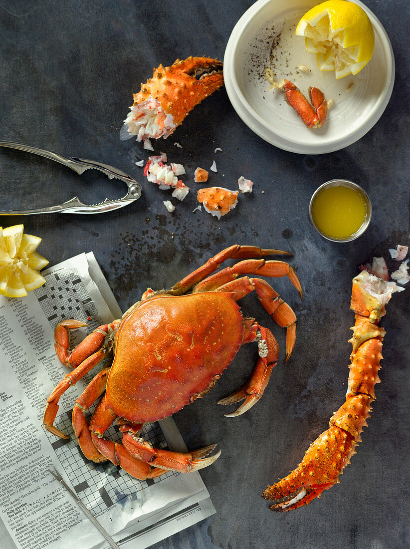 Cooked crab with a pair of crab crackers, melted butter and lemon (seen from above)