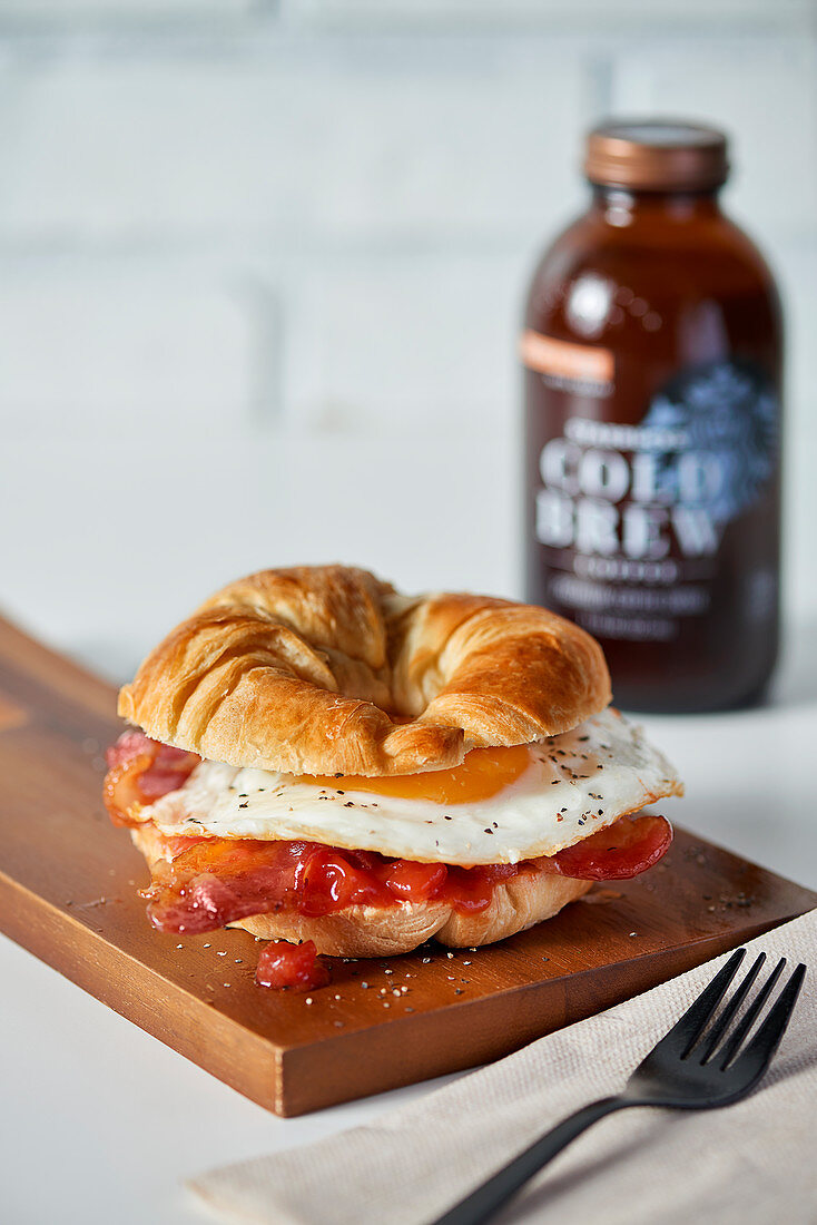 A croissant sandwich with bacon and fried eggs for breakfast