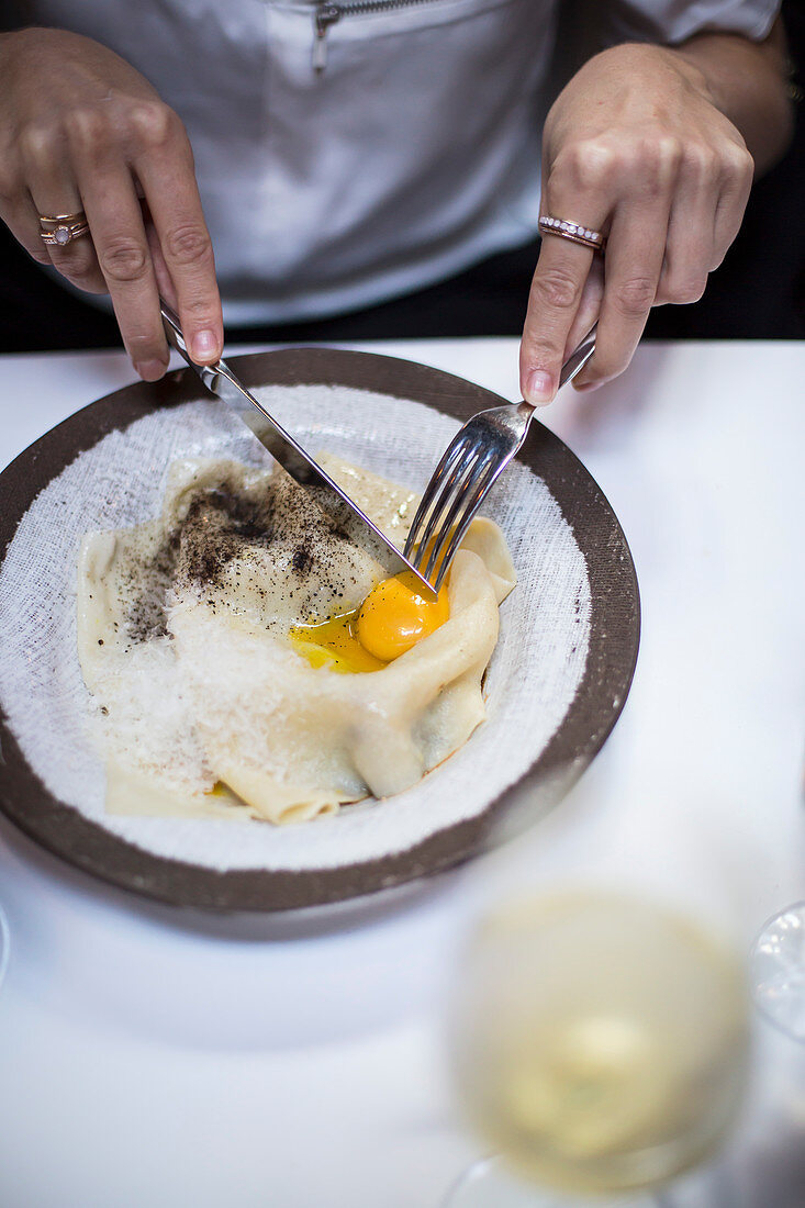 A woman eating pasta with an egg yolk at a restaurant table