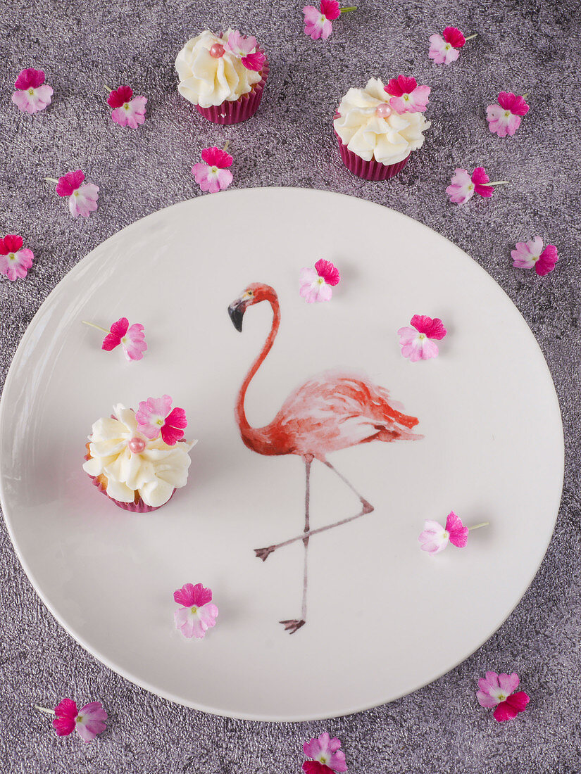 Mini cupcakes with redcurrants and cream on a flamingo plate