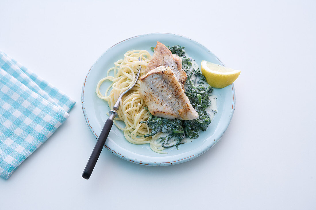 Rose fish on a bed of spinach with cream cheese and spaghetti