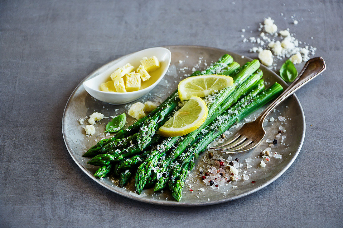 Tasty cooked green asparagus with parmesan cheese, lemon and spices