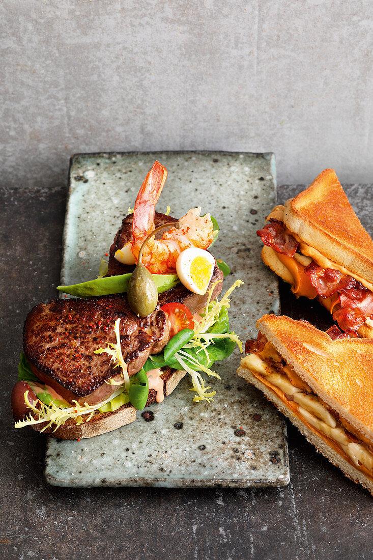 Peanut butter, bacon and banana sandwiches and an open beef tenderloin sandwich