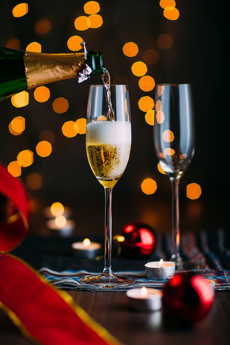 Glasses of champagne with candles and Chrsitmas decoration