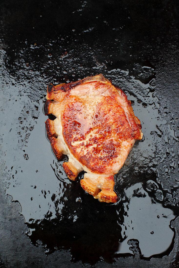 A grilled pork chop on a dark surface