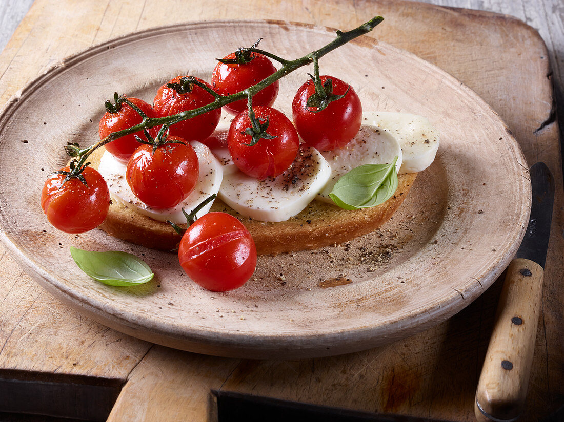 A slice of bread topped with tomatoes, mozzarella and basil