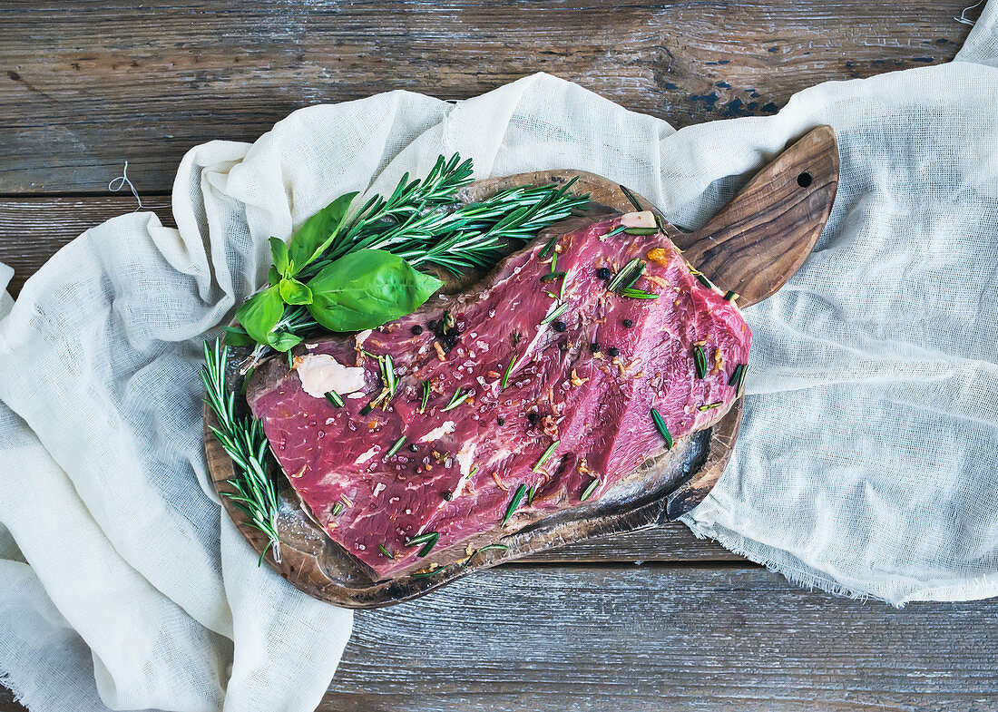 A piece of raw fresh beef (Ribeye steak) marinated in spices and herbs