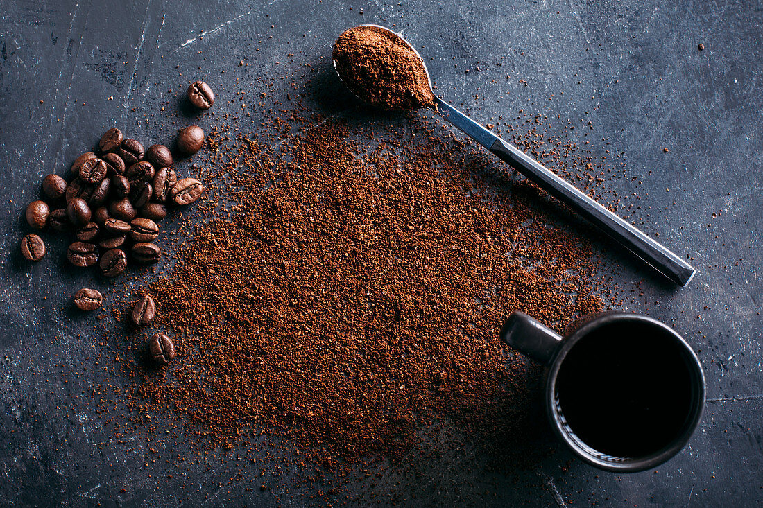 Coffee beans and ground coffee on dark background