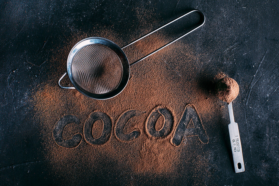 Kakaopulver mit Schriftzug 'Cocoa', Messlöffel und Sieb