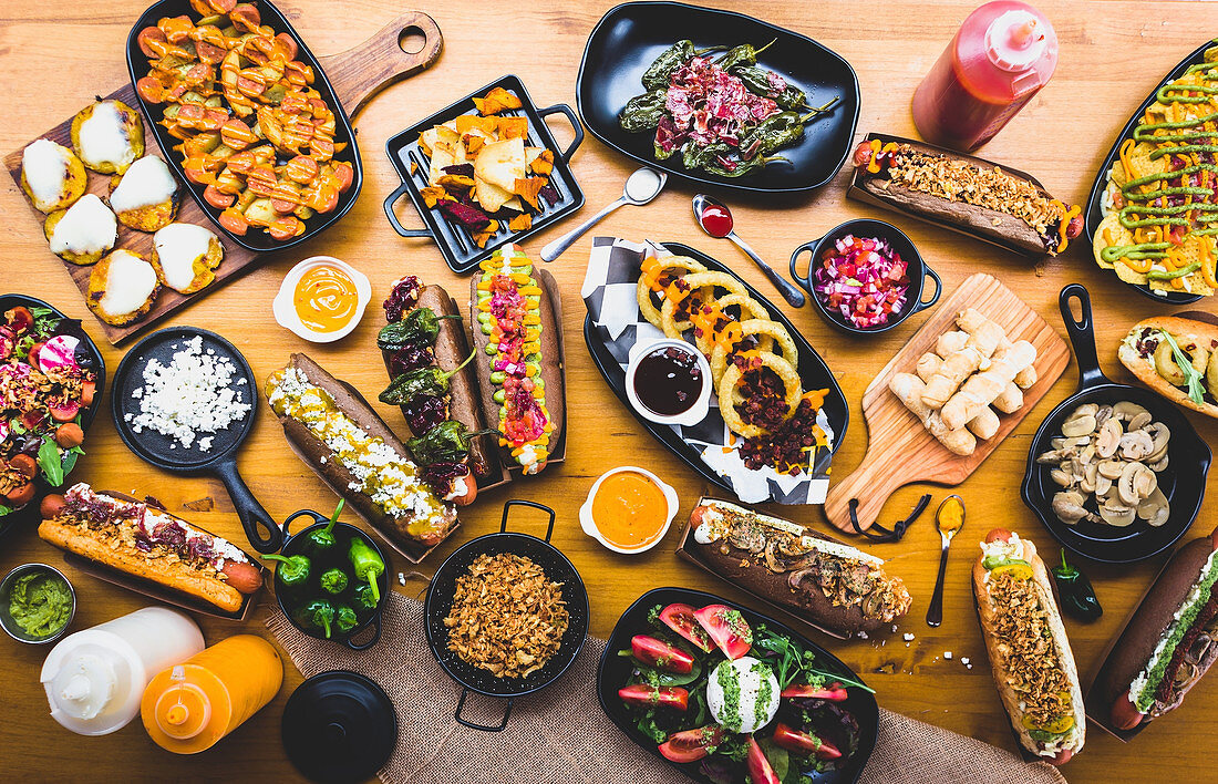 Flat lay of table served with great amount of various snacks and hot dogs with sauces and spices