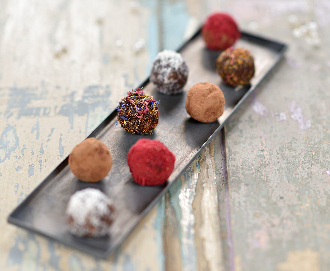 Chocolate date and walnut balls with cocoa, coconut, dried petals and fruit powder