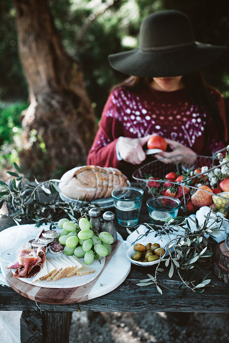 Woman in black hat sitting at table and cutting fruits and vegetables for lunch