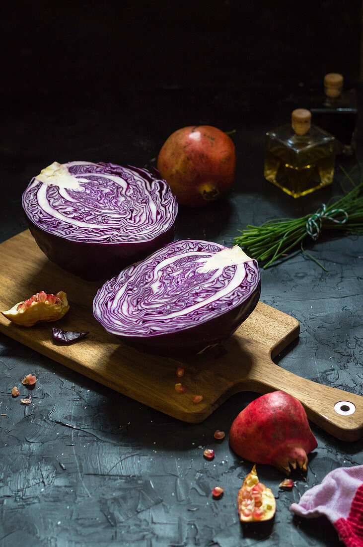Halved red cabbage on cutting board with pomegranate and chives