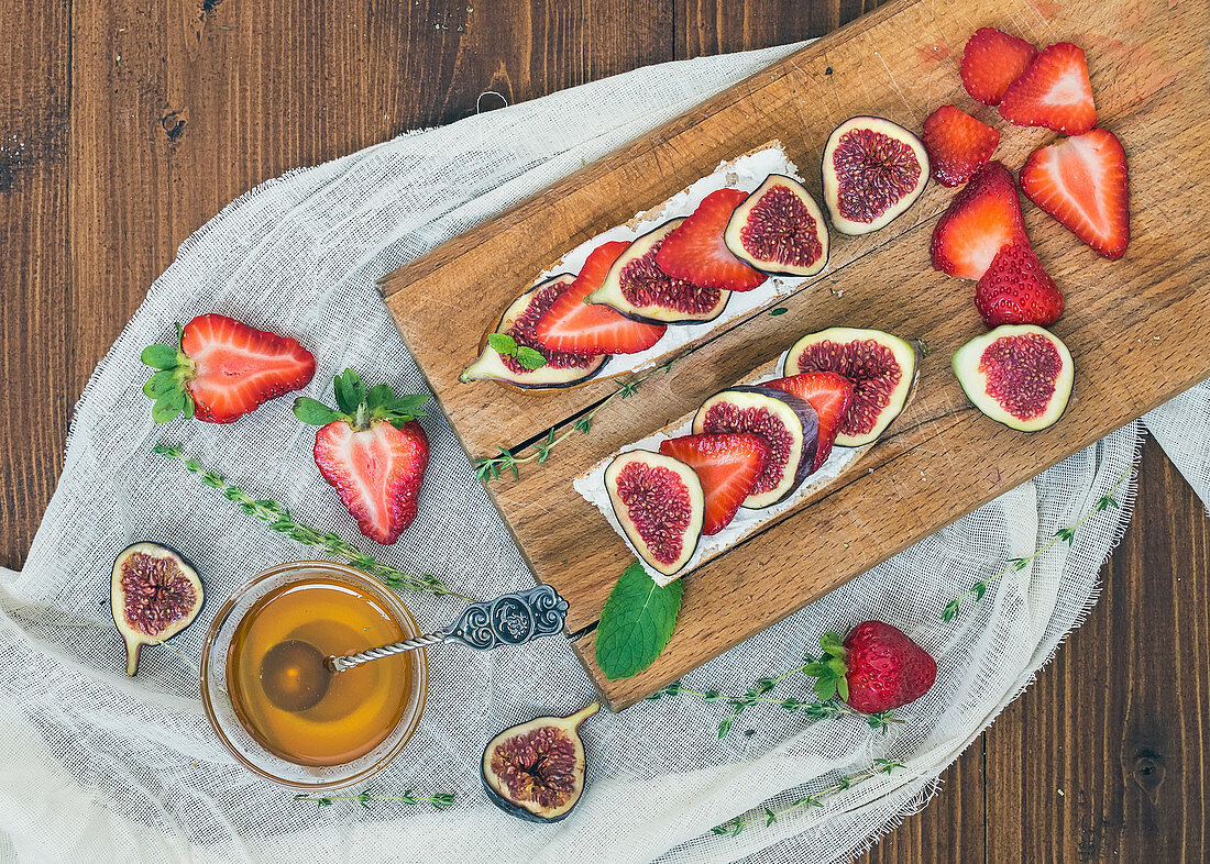 Fresh strawberries, figs, mint leaves, thyme and a small bawl of honey ob a wooden cutting board