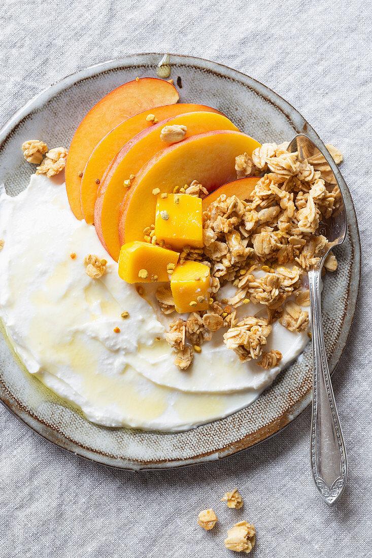 Greek yogurt, peach, mango and granola with honey and bee pollen, gluten free