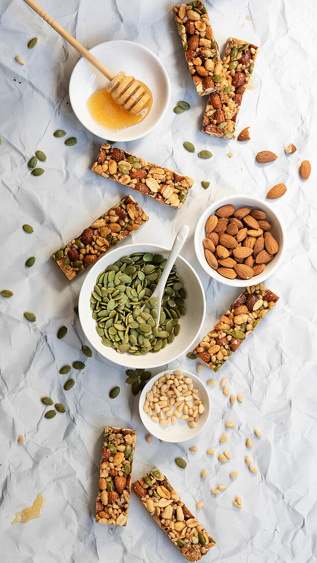 Honey nut bars with ingredients in small bowls