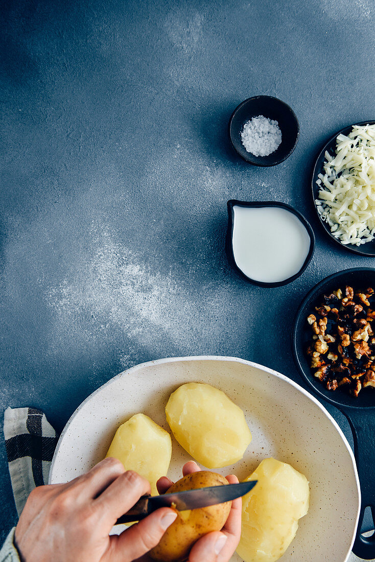 Hands peeling cooked potatoes with a knife in a white ceramic bowl