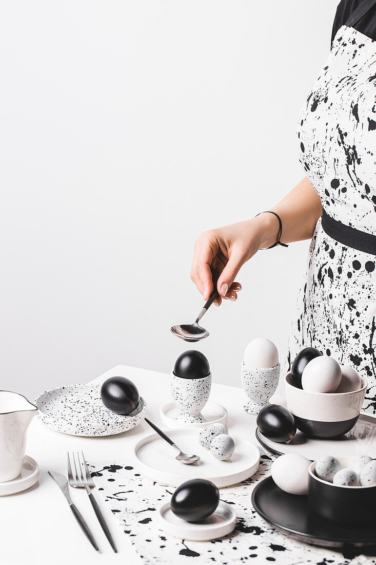 A woman wearing an apron in front of a table laid in black-and-white with coloured eggs