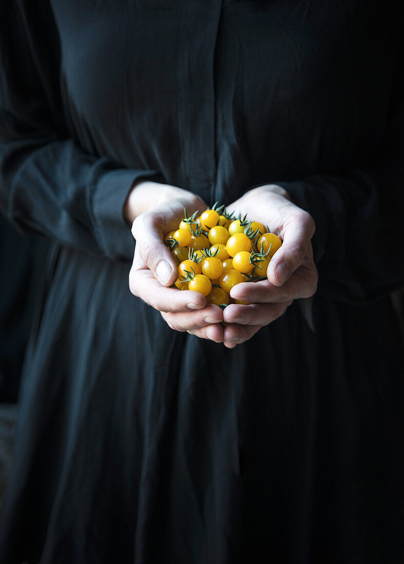 A woman holding yellow cherry tomatoes