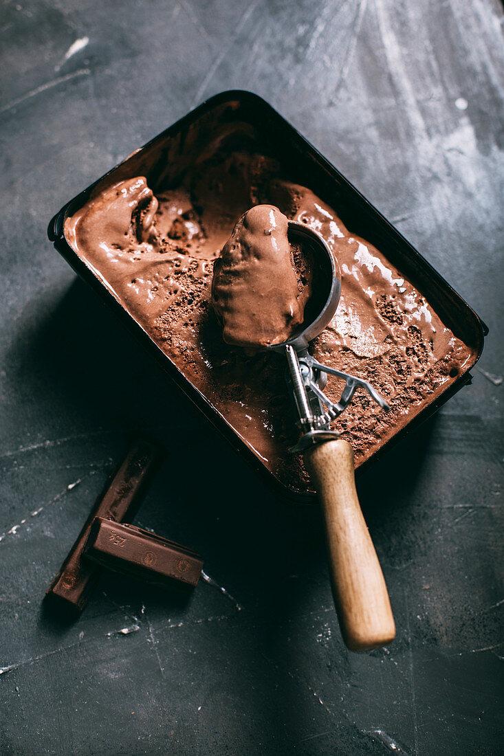 Chocolate ice cream in a scoop on dark background