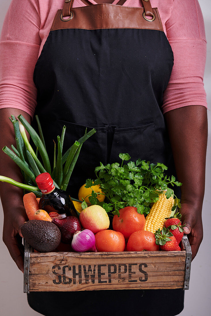 An African woman holding a wooden crate with vegetables, fruit and other foodstuff