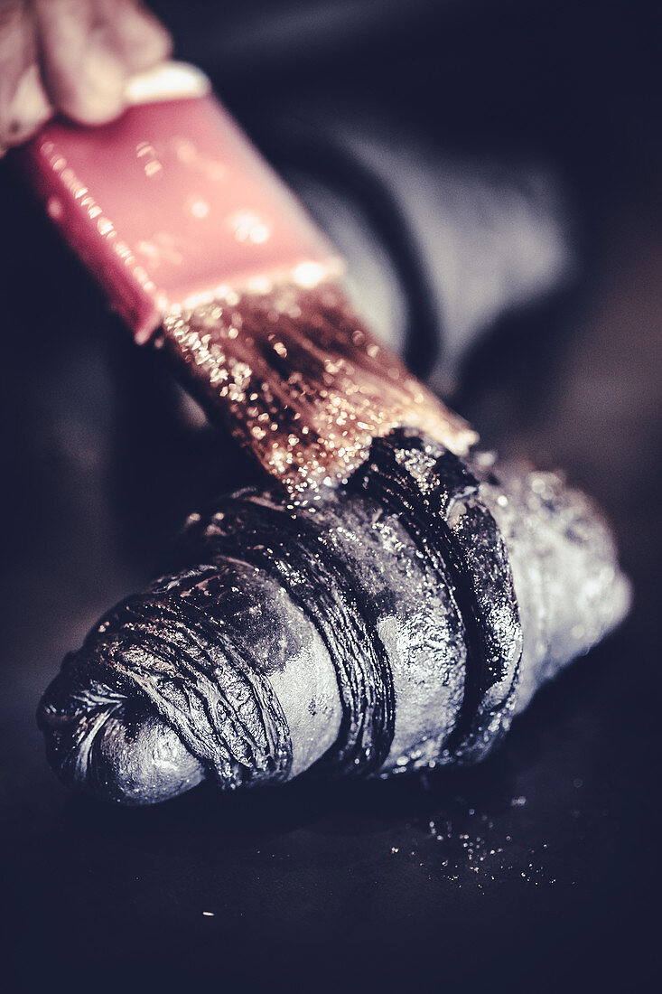 Black croissants with active charcoal powder being made: croissants being brushed with butter