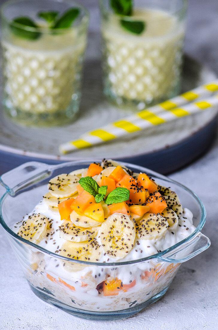 Porridge with yoghurt, papaya pieces, bananas and chia seeds and pineapple smoothies