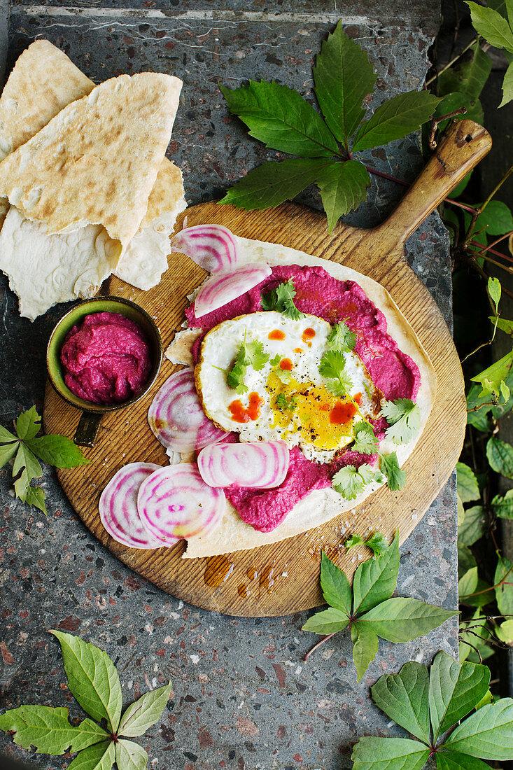 Beetroot hummus with fried egg and radicchio on flatbread