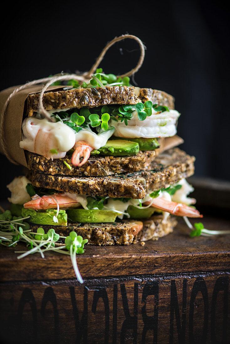 Prawn and avocado sandwich on a crunchy health bread with kombucha in the background