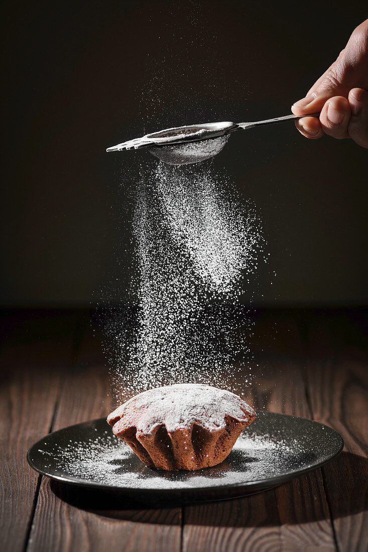 Man sprinkles icing sugar over biscuits
